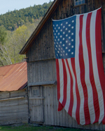 American flag hanging on a rustic barn
